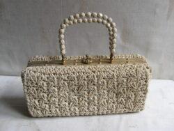 Vintage handtas, jaren 60/70, met kralen aan het handvat. Met sluiting in koper. Gebruikte staat maar heel. Lengte 27 cm, hoogte 13 cm, diep 7 cm.